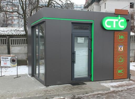На фото газовая заправка СТС серого цвета с зеленым логотипом, где установлены датчики охранной сигнализации
